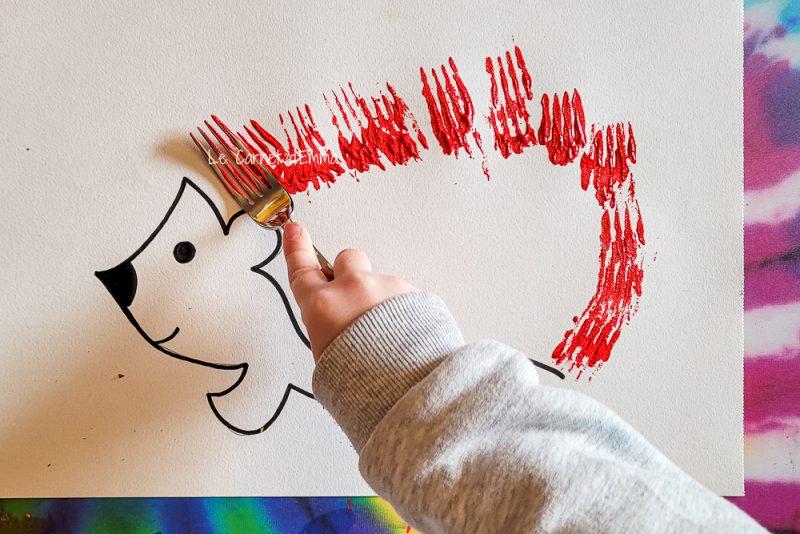 l'enfant peint les pics de l'hérisson avec une fourchette